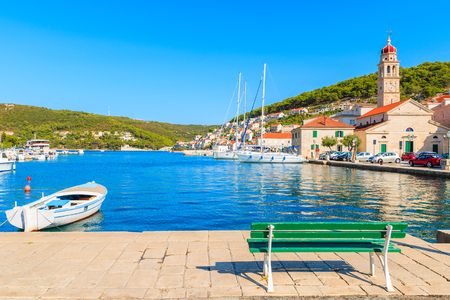 Bench and fishing boat on sea in beautiful port of Pucisca, Brac island, Croatia