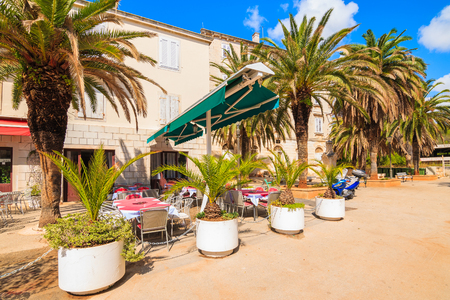 Restaurant building with palm trees in Milna port on Brac island, Dalmatia, Croatia