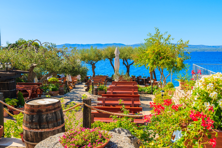 Traditional restaurant decorated with flowers and wine casks with sea view in Bol town, Brac island, Croatia