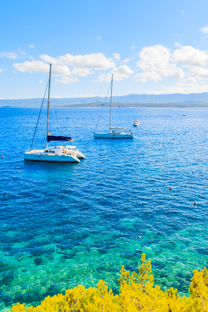 Boats on azure sea near Zlatni Rat beach at Bol, Brac island, Croatia