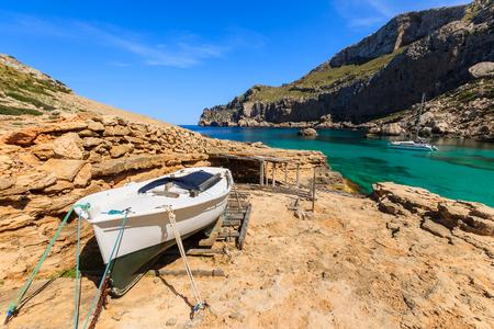White fishing boat in beautiful bay beach turquoise sea mountains, Cala Figuera on Cap Formentor, Majorca, Spain Stock Photo