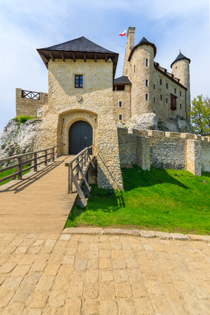 Wooden bridge entrance to beautiful Bobolice medieval castle on sunny day, Poland Editorial