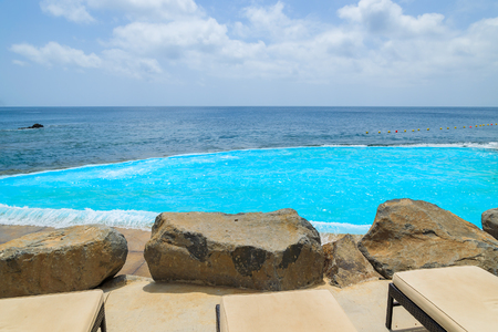 Sunbeds with lava rocks and turquoise water of infinity swimming pool at coast of Atlantic Ocean, Madeira island, Portugal