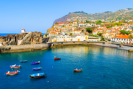 View of Camara de Lobos port with colourful fishing boats on sea, Madeira island