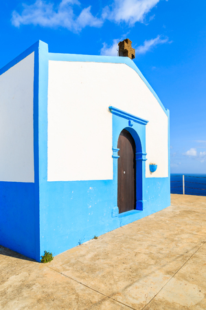 White and blue colour small church on top of a cliff near Canical town on coast of Madeira island, Portugal