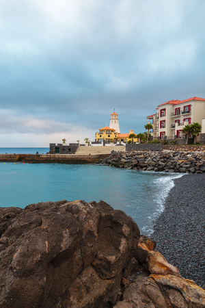 Black stone volcanic beach lighthouse view cloudy sky on east coast of Madeira island, Portugal