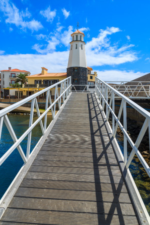Wooden pier to lighthouse in marina with colourful houses of Portuguese village, Madeira island, Portugal