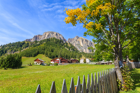 Wooden fence on green meadow with traditional alpine houses in distance in summer landscape of Dolomites Mountains, Italy