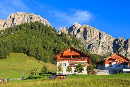 Traditional houses in alpine village on sunny summer day, Colfosco, The Dolomites Mountains, Italy