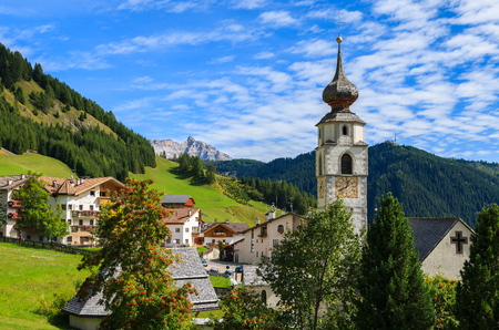 Church in Colfosco village on sunny day with Dolomites mountains in the background, South Tyrol, Italy