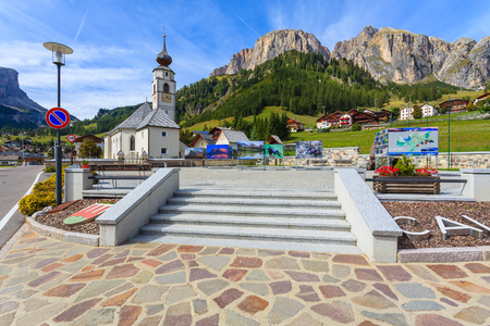COLFOSCO, SOUTH TYROL - SEP 22, 2013: square with church in alpine village, Dolomites Mountains (The Alps), Italy. Every September photography exhibition takes place here showcasing mountain images.