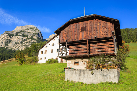 Farm houses on green meadow with Dolomites Mountains in the background, Corvara, Trentino Alto Adige, Italy