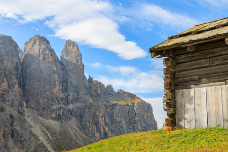 Wooden barn on green pasture in Dolomites Mountains, Italy