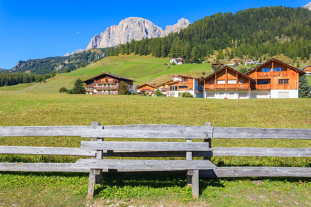 Wooden bench and pasture fence in alpine La Villa village with houses and Dolomites Mountains in the background, Italy