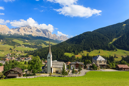 View of La Villa village church in Dolomites Mountains, Italy Фото со стока