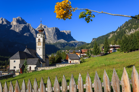 View of church in Colfosco village on sunny day with mountains in the background, Trentino Alto Adige, Italy