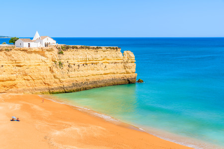 View of beach with rock cliffs and white church in Armacao de Pera town, Algarve, Portugal