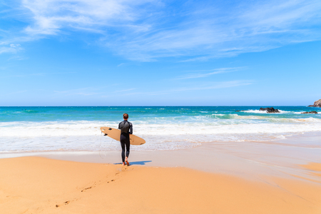 PRAIA DO AMADO BEACH, PORTUGAL - MAY 15, 2015: Surfer walking on Praia do Amado beach with ocean waves hitting shore. Algarve region is popular holiday destination in southern Europe. 版權商用圖片 - 97264147