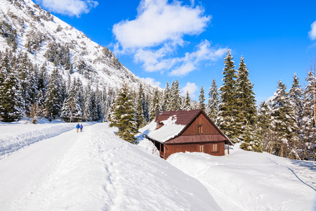Couple of tourists on snowy road and mountain house near road to Morskie Oko lake in winter season, Tatra Mountains