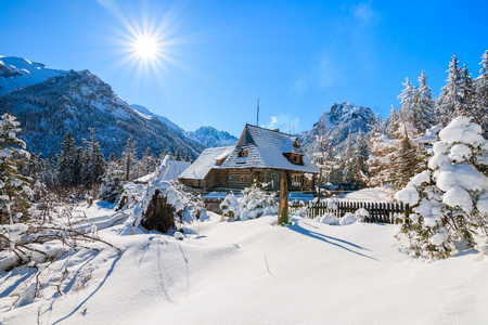 Small wooden house in winter landscape near Morskie Oko lake with sun on blue sky, Tatra Mountains, Poland