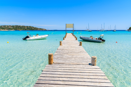 Wooden jetty with boats on Santa Giulia beach, Corsica island, France 写真素材