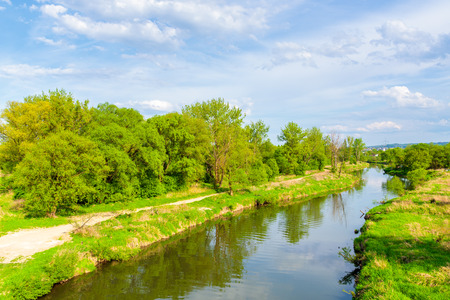 View of Vistula river and green fields near Tyniec village in springtime, Poland