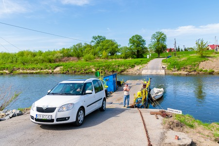 VISTULA RIVER, POLAND - APR 28, 2018: Car leaving small ferry which is transporting people and vehicles across the river on sunny spring day. This place is located near Krakow city.