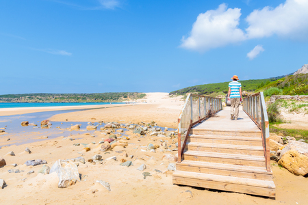 Young woman tourist walking on coastal promenade on Bolonia beach, Andalusia, Spain Stock Photo