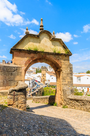 Castle gate and view of white houses in Andalusian village of Ronda, Spain
