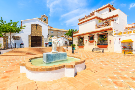Water fountain on square with church building in Estepona town, Costa del Sol, Spain Stock Photo