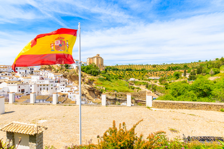 Spanish flag waving on wind and view of beautiful white village with church on hill, Sentinel de las Bodegas, Andalusia, Spain Stock Photo