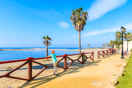 Young woman tourist standing on coastal promenade along beautiful beach near Marbella, Andalusia, Spain