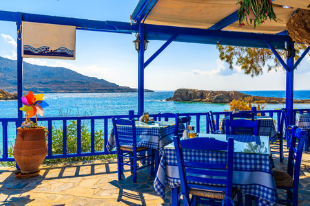Terrace with tables in traditional Greek tavern with sea view in Lefkos village on Karpathos island, Greece 스톡 콘텐츠