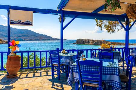 Terrasse mit Tischen in traditioneller griechischer Taverne mit Meerblick im Dorf Lefkos auf der Insel Karpathos, Griechenland Standard-Bild