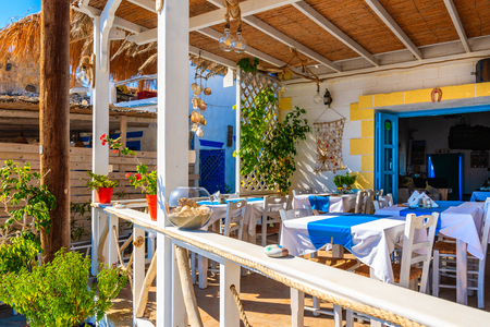 Tables in traditional Greek tavern in Finiki port, Karpathos island, Greece Stock Photo