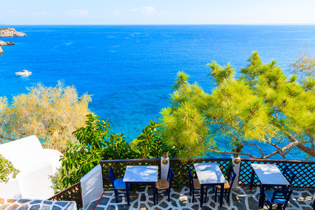 Terrace with tables in traditional Greek tavern in Kyra Pynagia bay with beautiful sea view on Karpathos island, Greece 免版税图像
