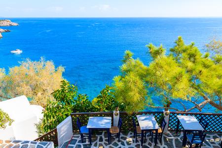 Terrasse mit Tischen in der traditionellen griechischen Taverne in der Bucht von Kyra Pynagia mit wunderschönem Meerblick auf der Insel Karpathos, Griechenland