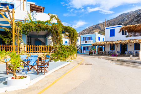 Street with traditional Greek houses and tavernas in Finiki port on Karpathos island, Greece Stock Photo