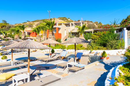 Umbrellas and sunbeds on beach in Ammopi village, Karpathos island, Greece