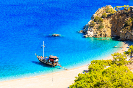 Tourist boat anchoring at beautiful Apella beach on Karpathos island, Greece Imagens - 115669927