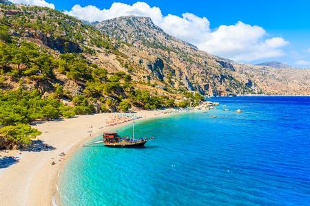Sailing boat anchoring at beautiful Apella beach on Karpathos island, Greece