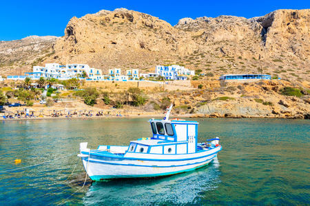 White typical fishing boat on turquoise sea water in Finiki port, Karpathos island, Greece