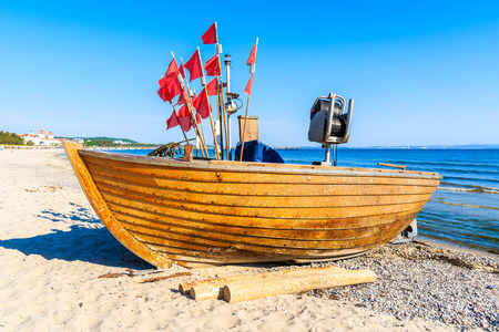Old wooden fishing boat on sandy beach in coastal holiday resort of Binz, Rugen island, Baltic Sea, Germany