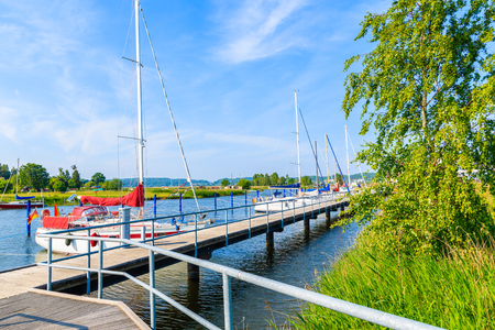 Pier with sailing boats anchoring on beautiful lake in Moritzdorf village on coast of Rugen island, Baltic Sea, Germany