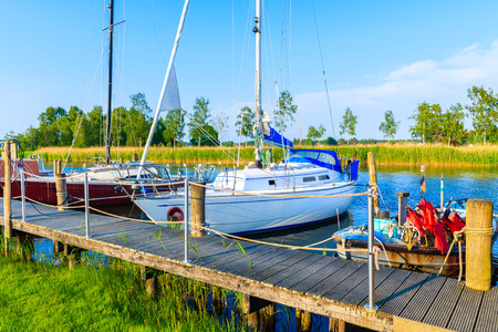 Sailing and fishing boats mooring at wooden pier on beautiful lake in Moritzdorf village on coast of Rugen island, Baltic Sea, Germany
