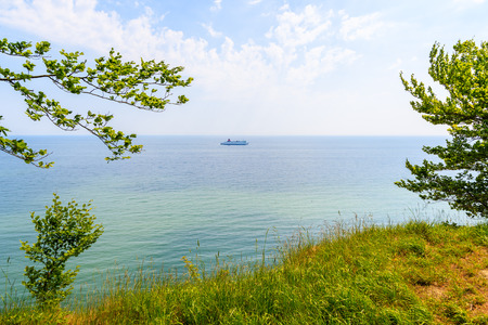 Ferry ship sailing on sea horizon seen from cliffs of Jasmund National Park, Ruegen island, Baltic Sea, Germany