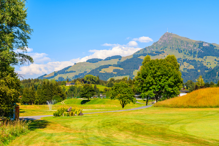 Green golf course area against mountains background on sunny summer day, Kitzbuhel, Tyrol, Austria 免版税图像