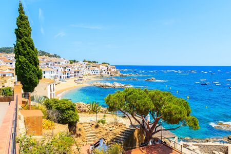 Amazing view of Calella de Palafrugell, scenic fishing village with white houses and sandy beach with clear blue water, Costa Brava, Catalonia, Spain Фото со стока