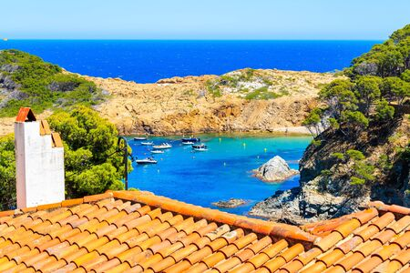 View of  Sa Tuna sea bay with orange tile roof in foreground, Costa Brava, Spain 写真素材