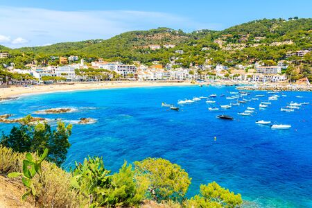 Beautiful bay with boats on sea and view of Llafranc village, Costa Brava, Spain